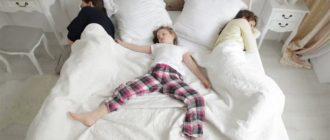 Ребенок на кровати посередине между стесненными им родителями